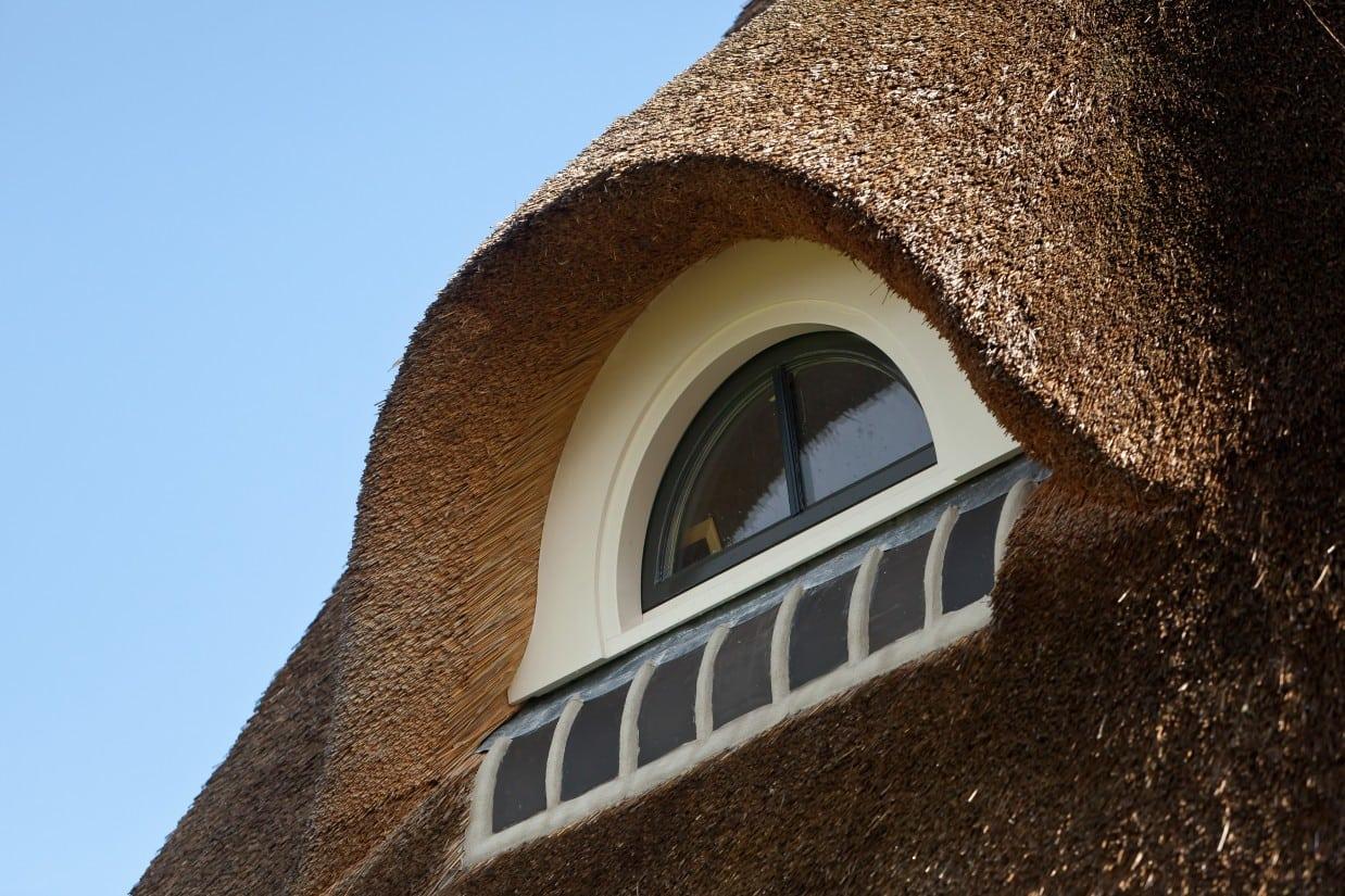 15. Rietgedekte villa bouwen, rietgedekte villa, prachtig dakkapel detail met grote nokvorsten afgewerkt.