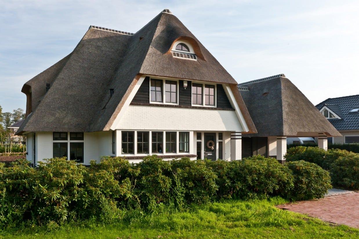 18. Rietgedekte villa bouwen, struiken, die de erfscheiding aangeven van deze prachtige villa