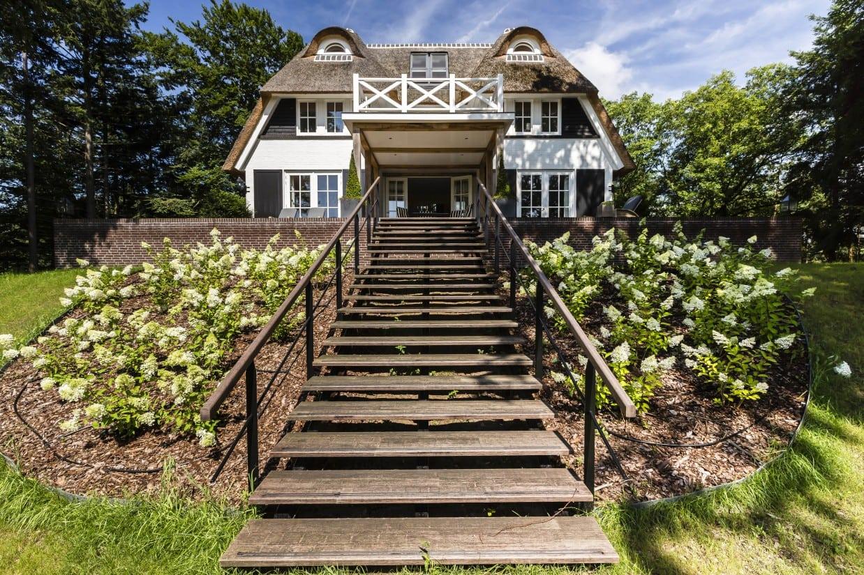 6. Rietgedekte villa bouwen, landhuis met stalen trap met houten tredes