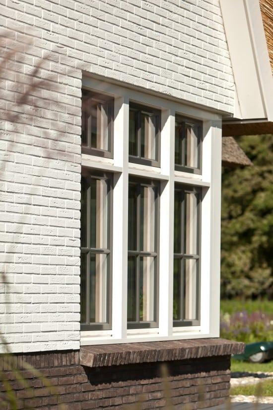 6. Rietgedekte villa bouwen, metselwerk met rollaag, witte gekeimde muren